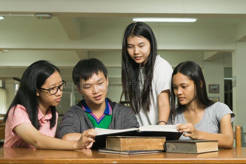 读一本书的一名严肃的年轻学生的画象在图书馆里 免版税图库摄影