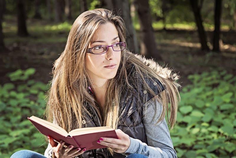 读一本书的美丽的女孩在秋天公园 库存图片