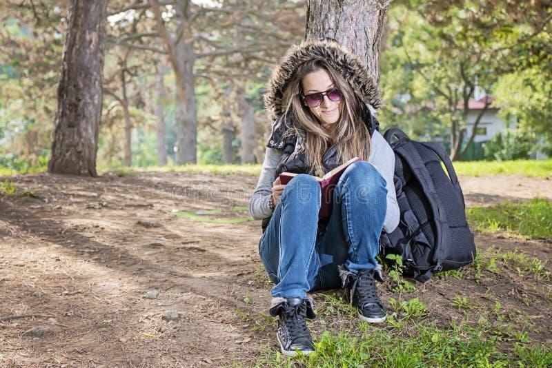 读一本书的美丽的女孩在秋天公园 免版税库存照片