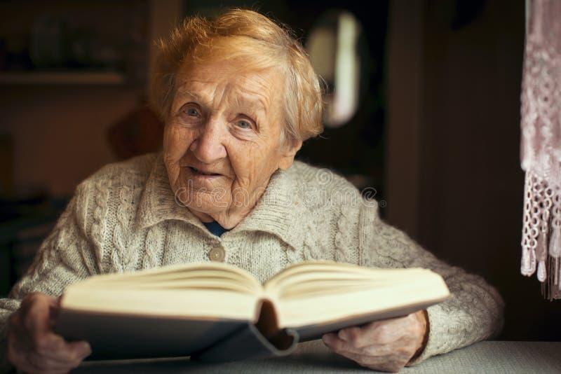 读一本书的退休的老愉快的妇女在您的房子里 免版税图库摄影