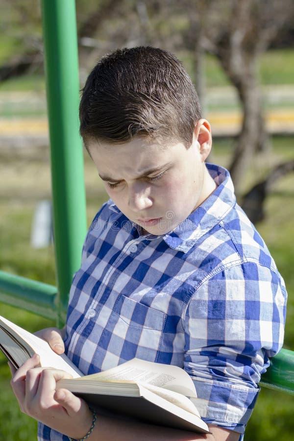 读一本书的年轻男孩在有浅景深的森林 免版税图库摄影