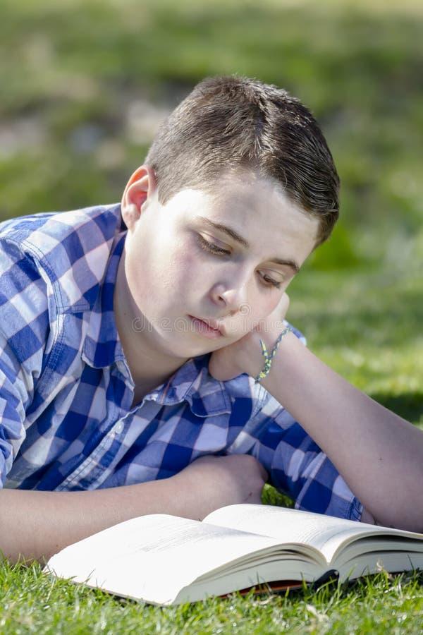 读一本书的年轻男孩在有浅景深的森林 图库摄影