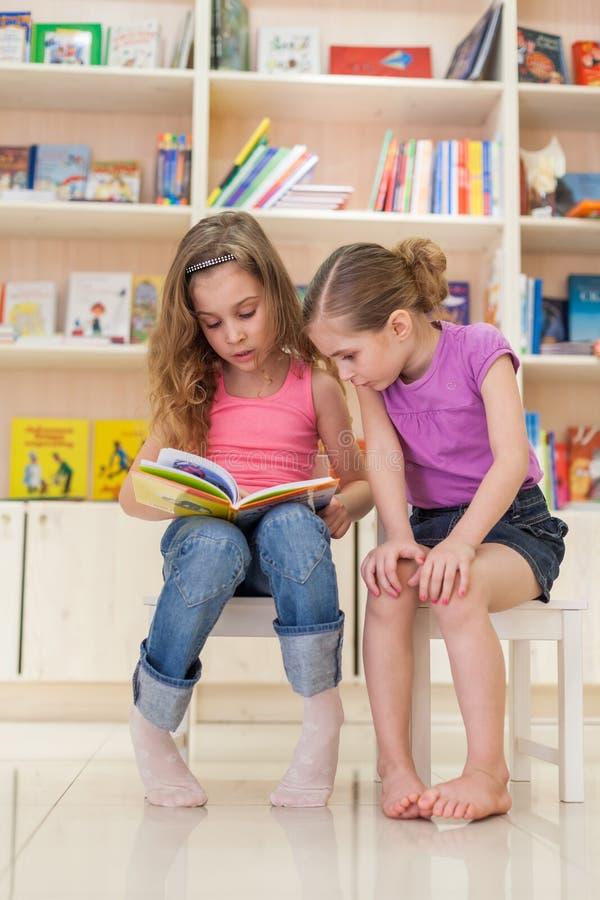 读一本引人入胜的书的两个女孩 库存照片