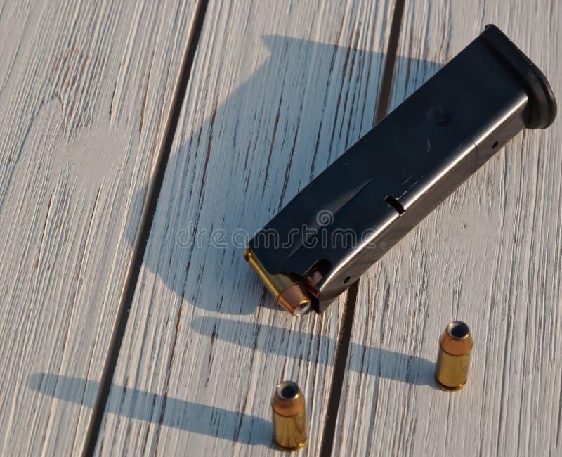 一本手枪杂志用在木背景的子弹 库存图片