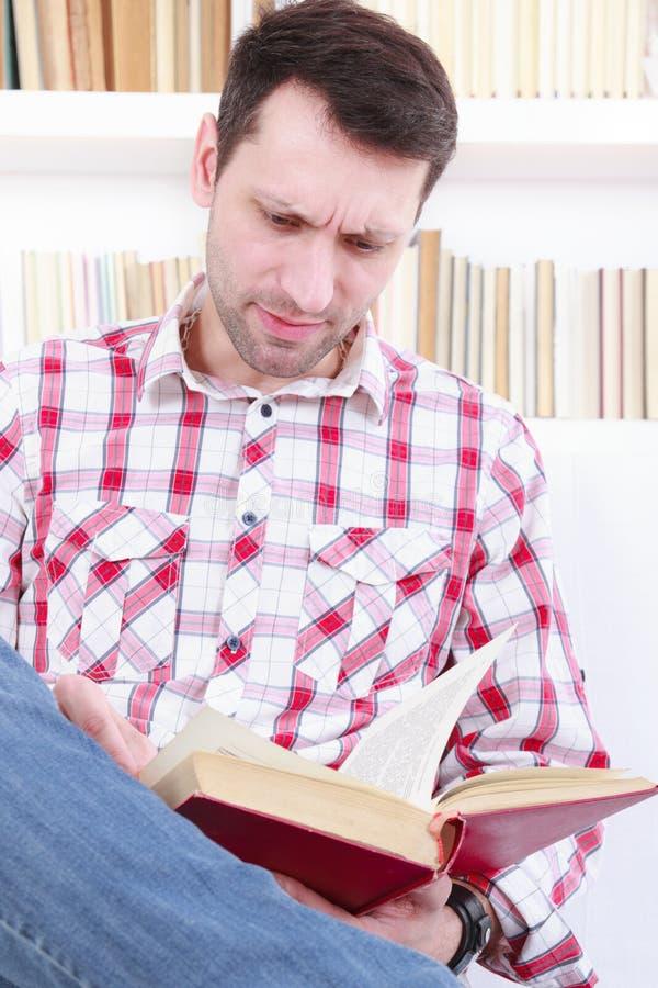 读一本新颖的书的偶然年轻人,当放松在沙发时 免版税库存图片