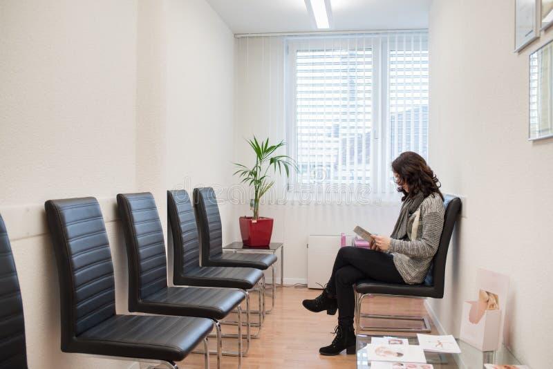 读一本杂志的患者在doctor's候诊室 图库摄影