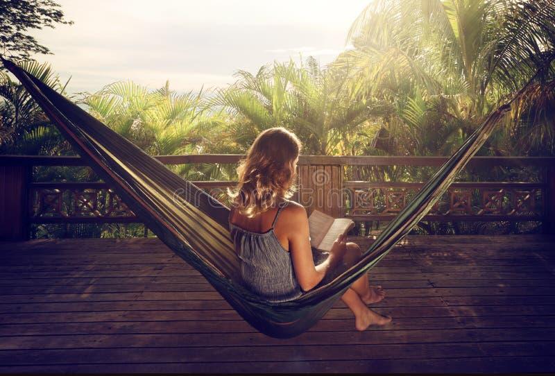 一本礼服阅读书的妇女在一个吊床在太阳的密林 免版税库存照片