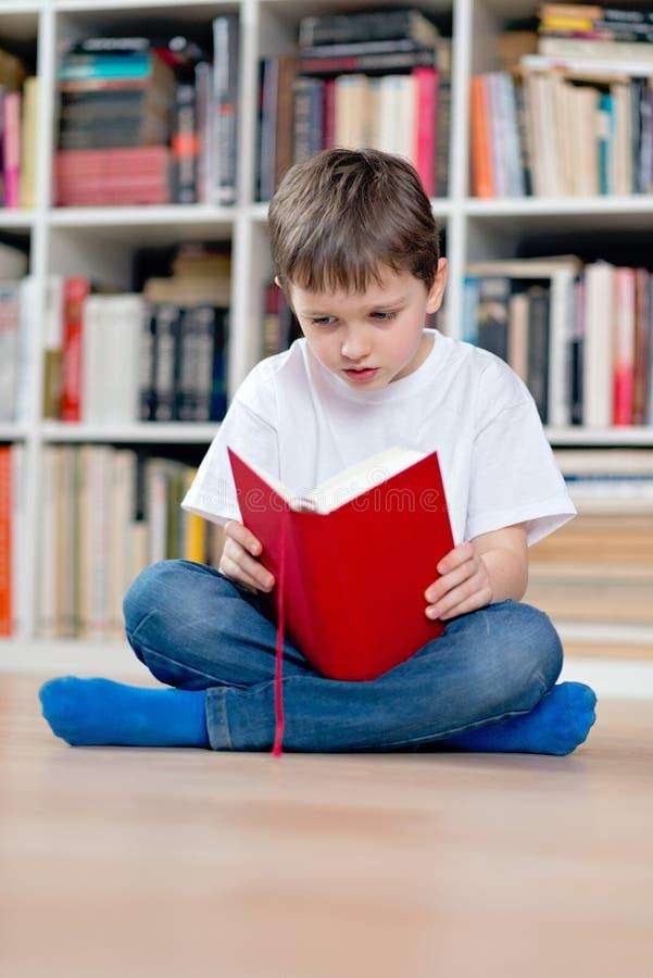 读一本红色书的小男孩孩子 库存照片