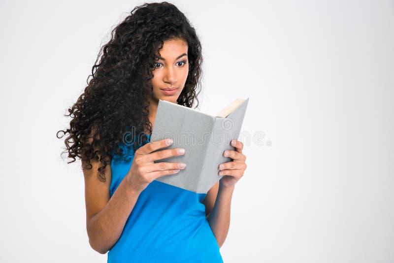 一本年轻美国黑人的妇女阅读书的画象 免版税库存照片