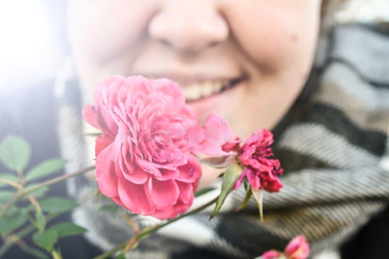 一朵光芒四射的桃红色花由看来是冷的一名微笑的愉快的妇女举行了 免版税库存照片