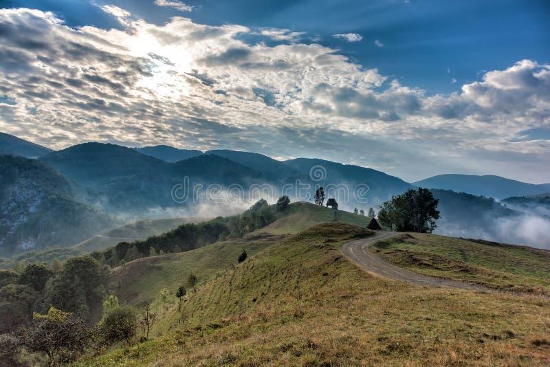 一朵有雾的早晨的美好的山风景与和老房子、树和云彩 免版税图库摄影