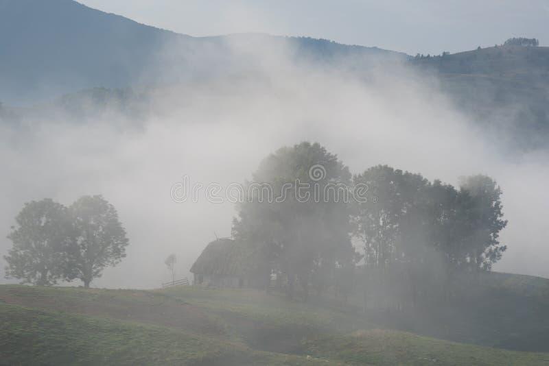 一朵有雾的早晨的美好的山风景与和老房子、树和云彩 库存照片