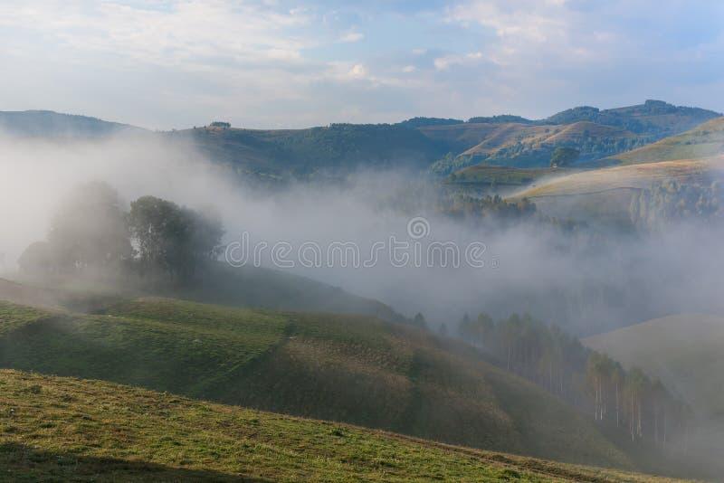 一朵有雾的早晨的美好的山风景与和老房子、树和云彩 免版税库存照片