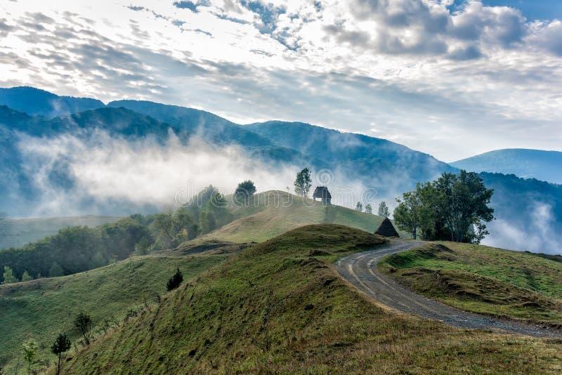 一朵有雾的早晨的美好的山风景与和老房子、树和云彩 图库摄影