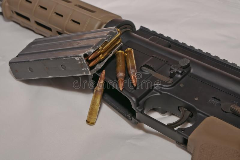 一杆黑和棕色223个口径AR-15步枪的鞋帮有一本被去除的,被装载的步枪杂志和三223枚口径子弹的在 免版税图库摄影