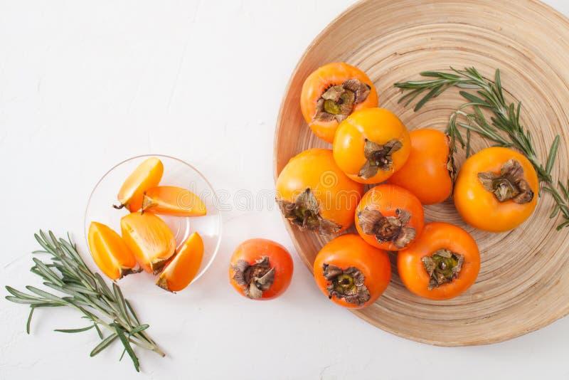 一束在一个碗的成熟柿子在一张白色桌上 库存照片