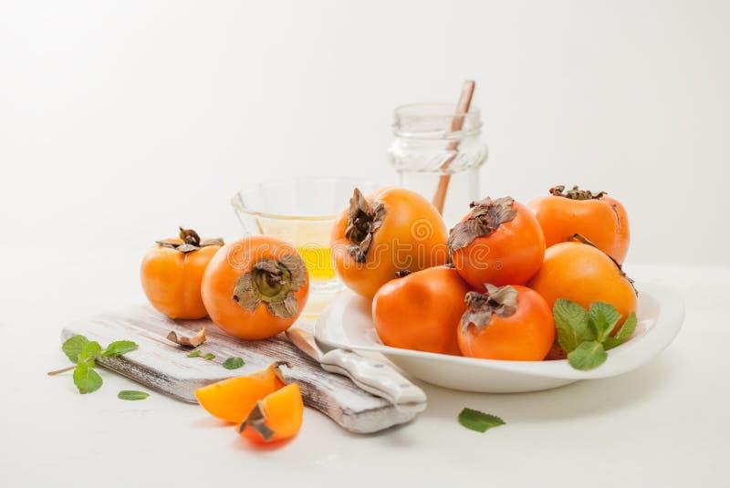 一束在一个碗的成熟柿子在一张白色桌上 免版税库存图片
