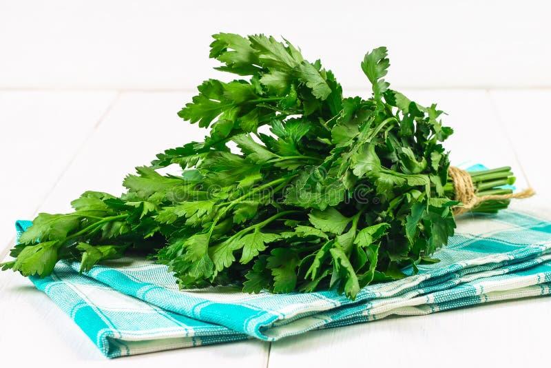 一束在一张白色木桌上的绿色荷兰芹 免版税库存照片