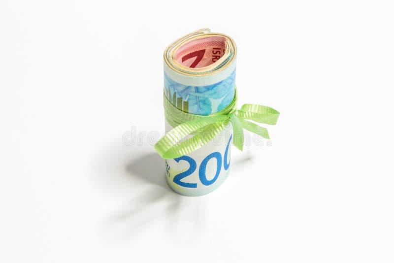 一束滚动另外价值新的以色列钞票在锡克尔NIS栓与被隔绝的绿色丝带在一白色backgro 库存图片