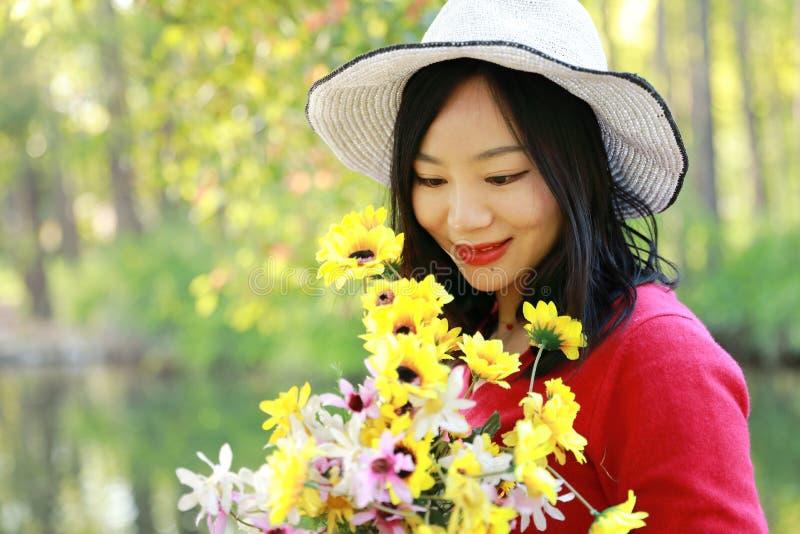 一束花由湖的步行在森林春天公园坐长凳享有舒适生活的愉快的亚洲中国妇女秀丽女孩微笑举行 免版税库存图片