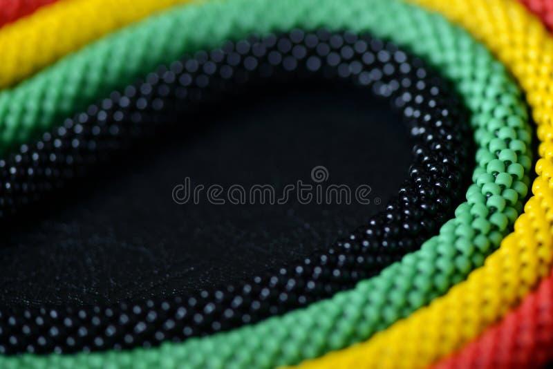 一条串珠的项链的片段在牙买加样式的在黑暗的背景 免版税库存图片