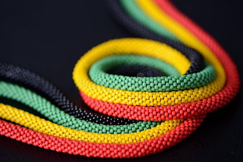 一条串珠的项链的片段在牙买加样式的在黑暗的背景 图库摄影