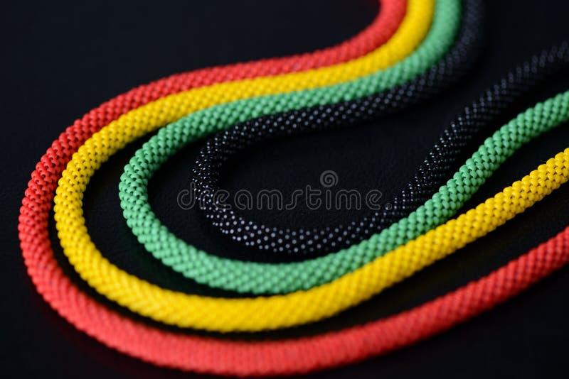 一条串珠的项链的片段在牙买加样式的在黑暗的背景 库存图片