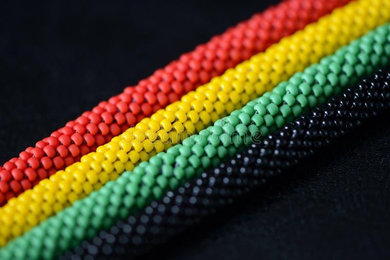 一条串珠的项链的片段在牙买加样式的在黑暗的背景 库存照片