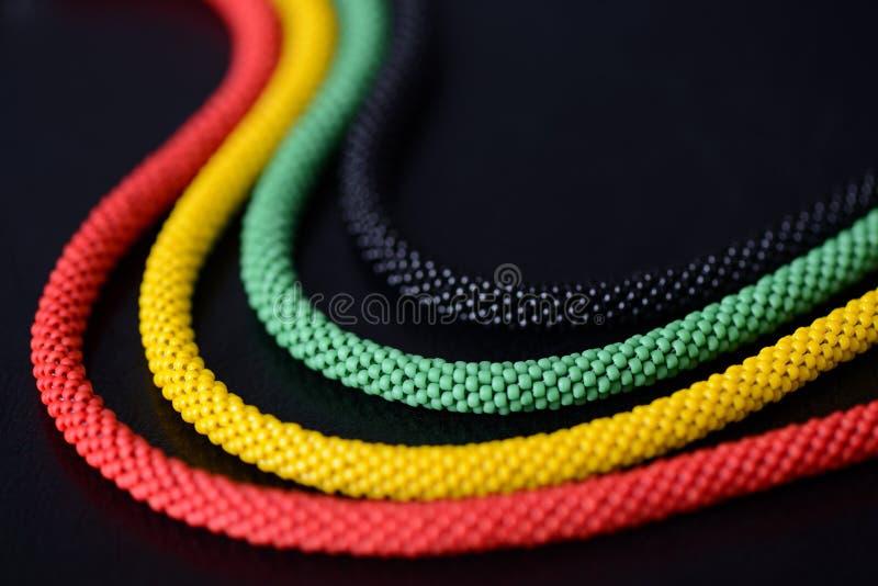 一条串珠的项链的片段在牙买加样式的在黑暗的背景 免版税图库摄影