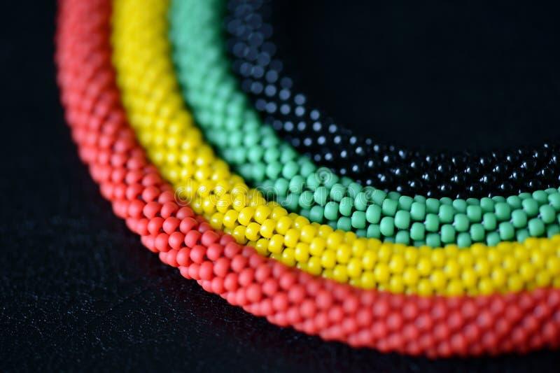 一条串珠的项链的片段在牙买加样式的在黑暗的背景 免版税库存照片