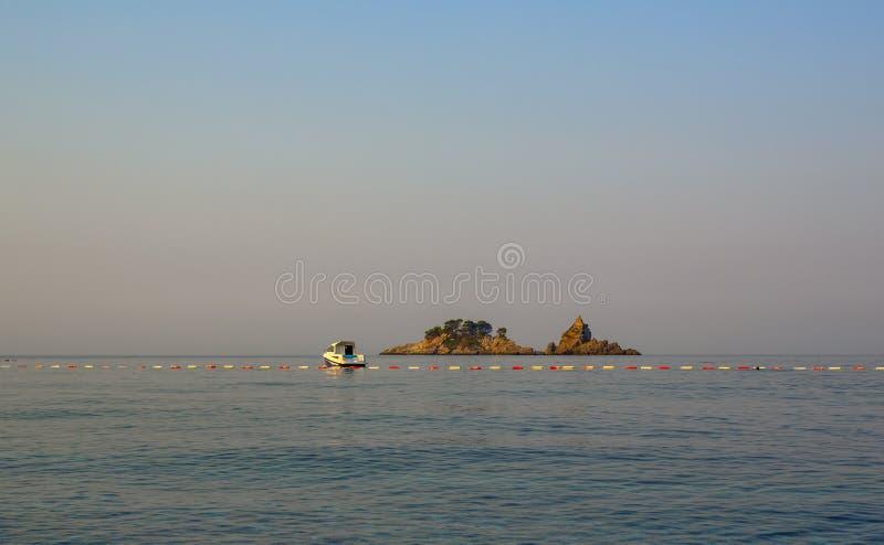 一条偏僻的小船接近了海岛 免版税库存照片