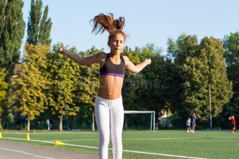 一条十几岁的女孩跳绳在学校体育场内 免版税库存图片