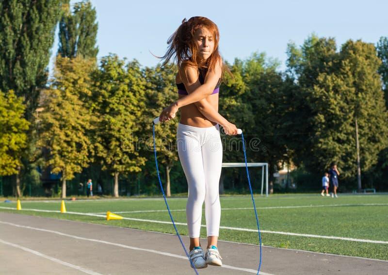 一条十几岁的女孩跳绳在学校体育场内 免版税库存照片