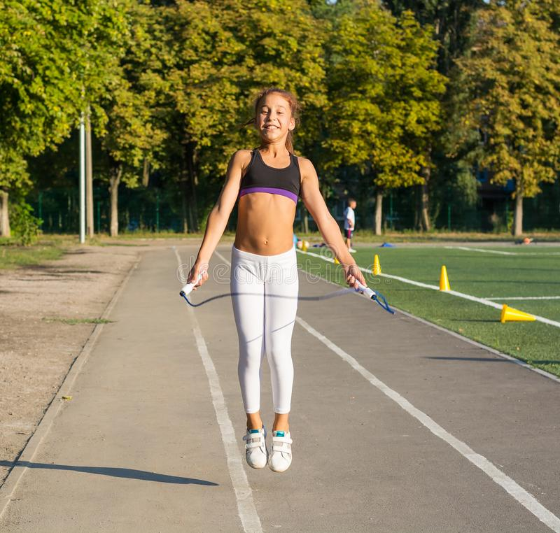一条十几岁的女孩跳绳在学校体育场内 库存图片