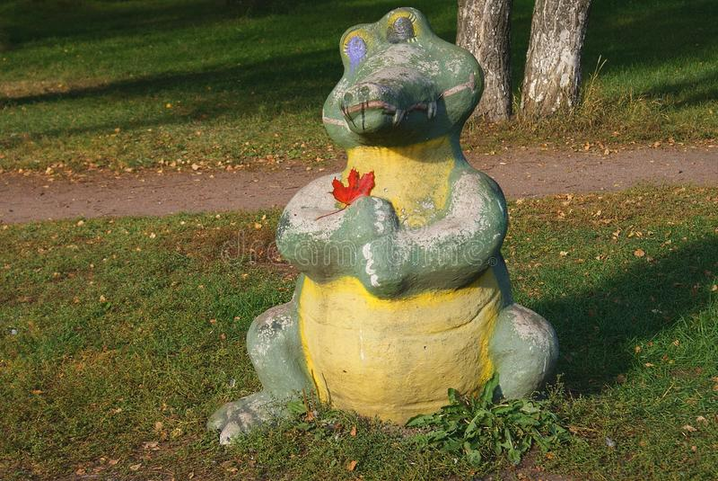 一条哀伤的鳄鱼的雕象在公园 图库摄影