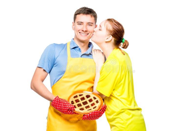 一条围裙的一个人用饼和她心爱的妻子,在白色的画象 库存图片