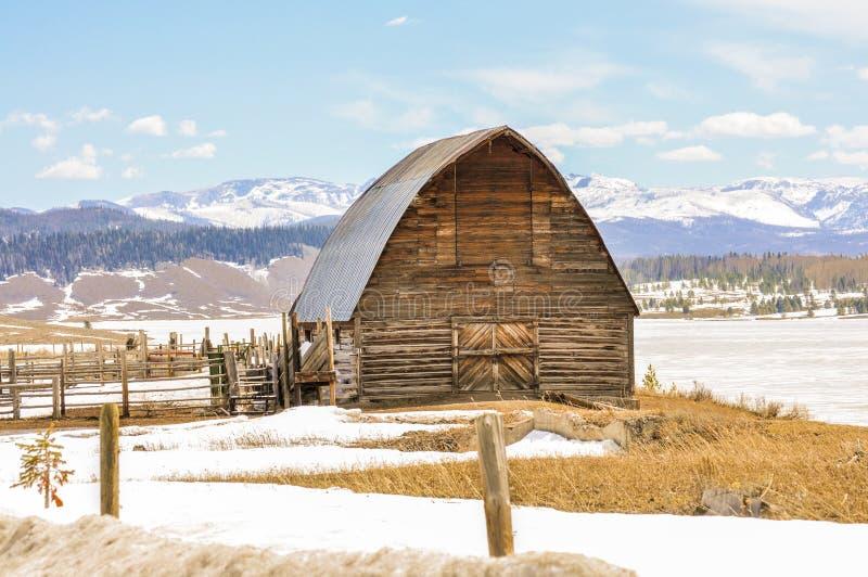 一条多雪的乡下公路的老谷仓 免版税库存照片