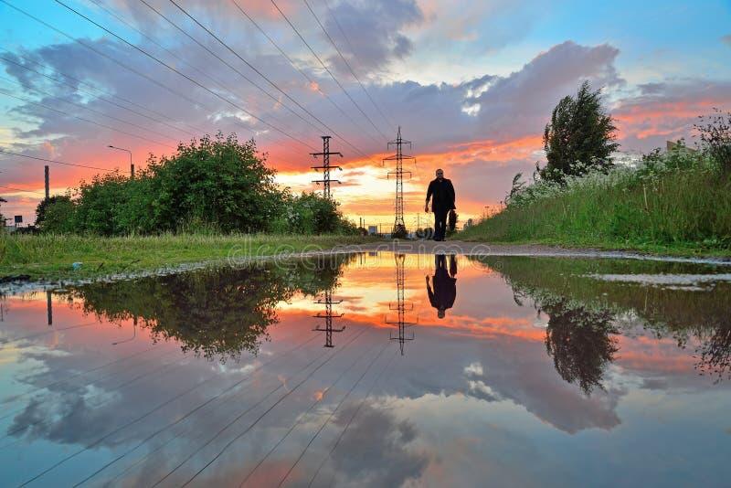 一条孤独的人和高压输电线-被反射的输电线 免版税库存照片