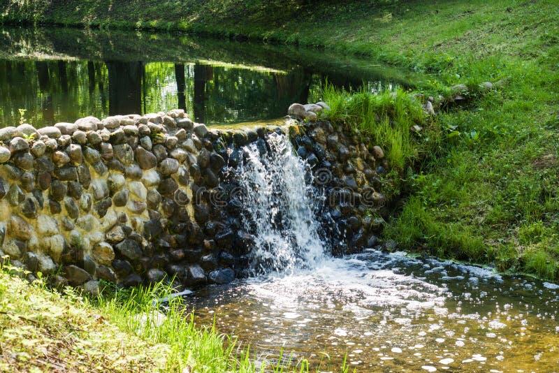 一条小河和人为瀑布在岩石 免版税库存图片
