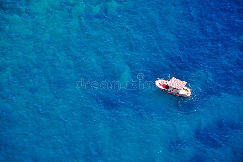 一条小船在蓝色海,卡普里岛海岛,意大利 库存图片