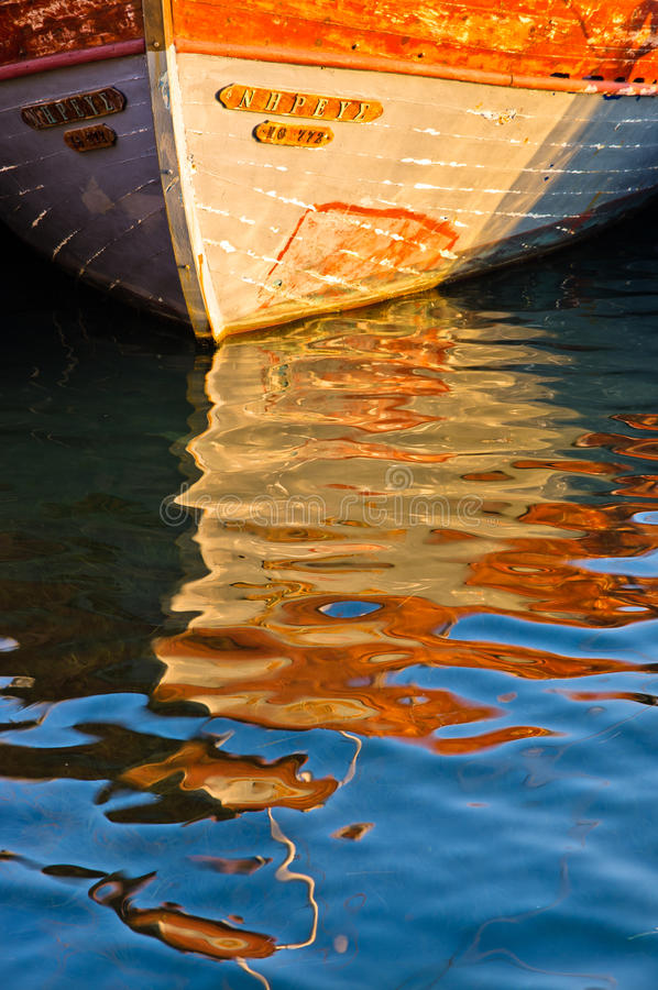 一条小船的反射在日落的作为液体抽象 库存图片