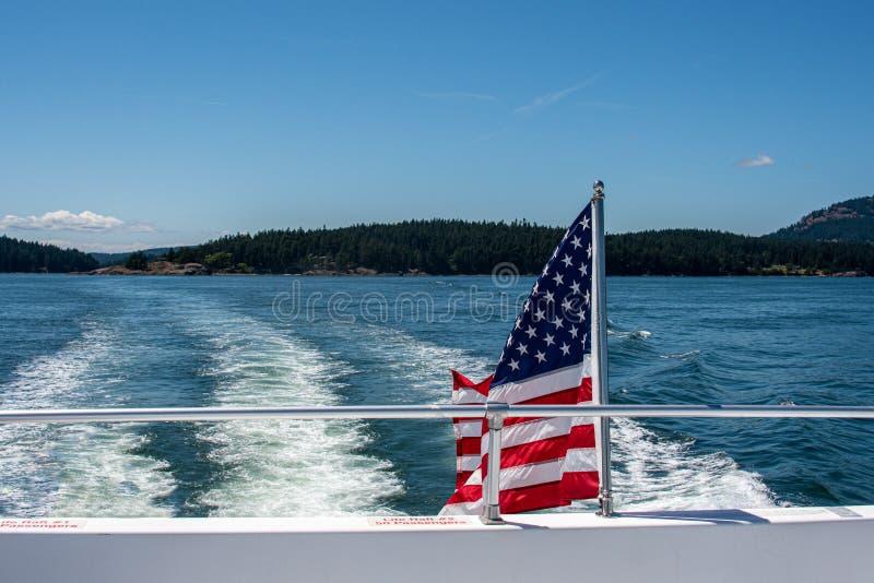 一条小船的后面的美国国旗飞行在Salish海的在圣胡安海岛在晴朗的天空蔚蓝天 免版税库存图片