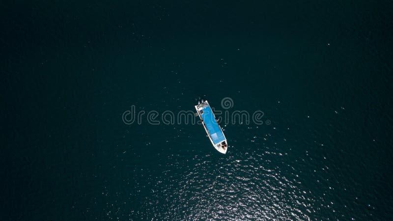 一条小船的寄生虫视图在深蓝色中间的 免版税库存照片