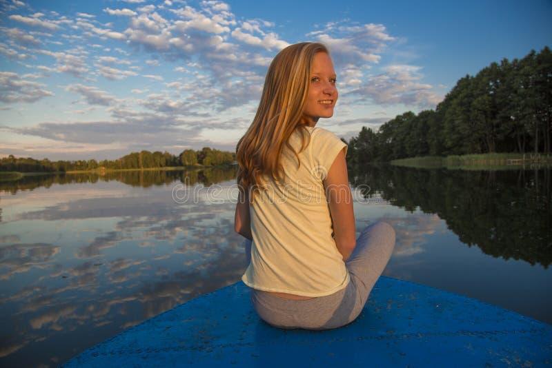 一条小船的青少年的女孩在湖 免版税图库摄影