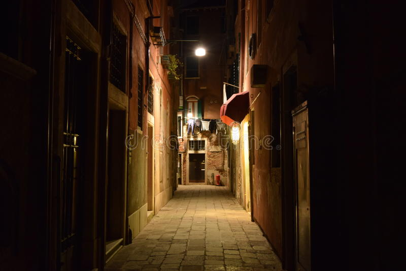 一条小街道在威尼斯在晚上 库存照片