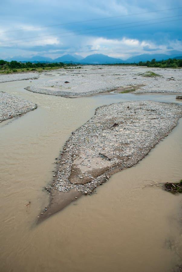 一条山河,肮脏的水的床反对山的在山河, 库存照片