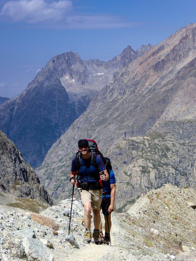 一条岩石和多灰尘的供徒步旅行的小道的男性远足者在法国阿尔卑斯 图库摄影