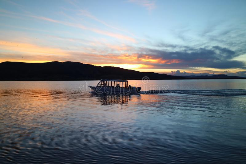 一条巡航的小船的剪影在的喀喀湖日落的,普诺,秘鲁的 库存照片