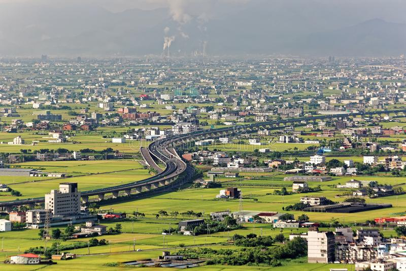 一条弯曲的高速公路通过与房子的绿色米领域驱散在平原中在宜兰,台湾 免版税库存照片