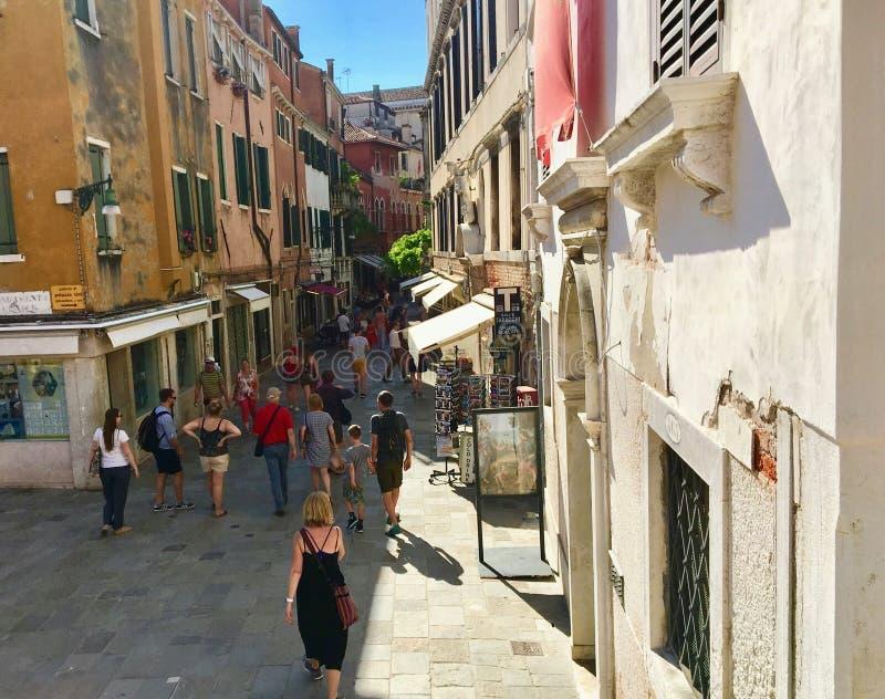 一条拥挤街道探索商店和餐馆的充分游人包围由美好的老威尼斯式建筑学 免版税库存图片